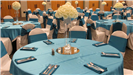 Turquoise and white wedding reception close up of a table setting with center pieces of white roses