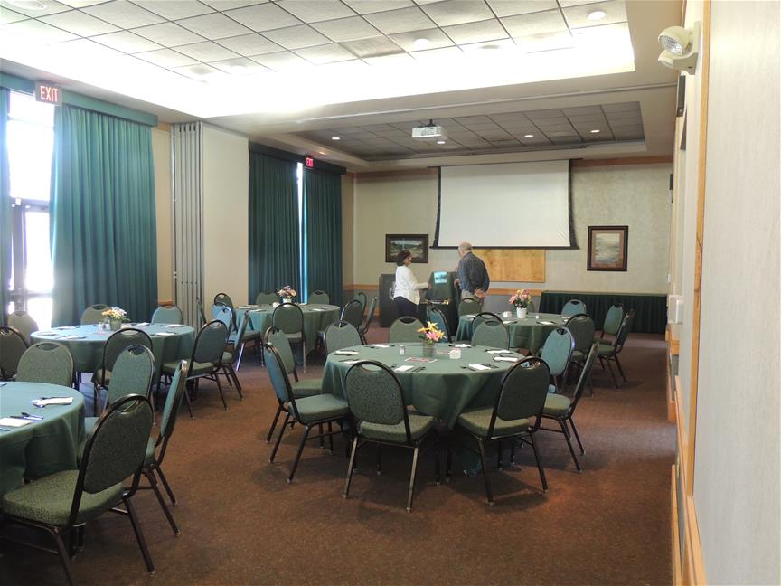 Banquet seating with round tables set-up with green table cloths and with AV Equipment